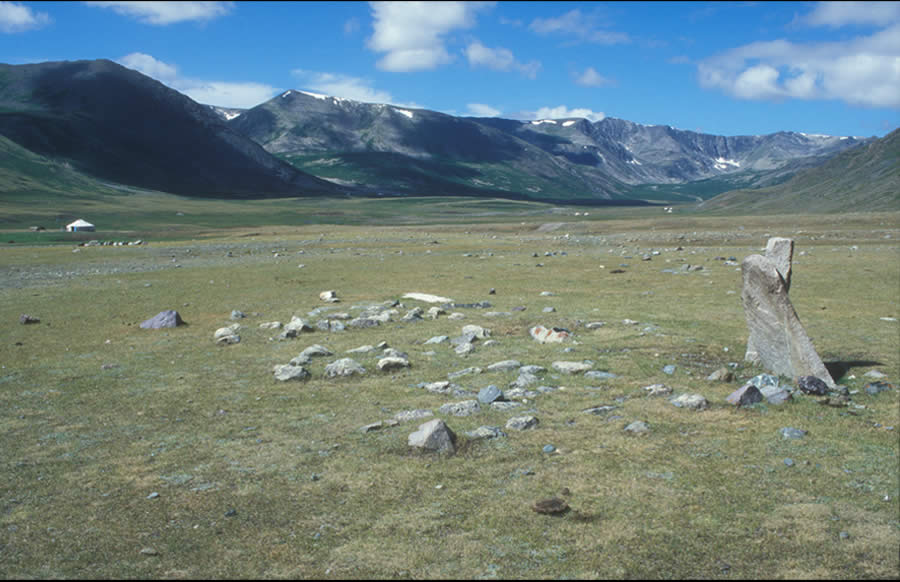 Small circles on the east side of two standing stones and several fallen stones. Bronze Age or later. Chigirtein Nuur. View southwest.Small circles were apparently used for sacrificial burned offerings, perhaps over a period of several thousand years. They are found alone or on the east side of standing stones or in multiple numbers on the north, west, south, and occasionally east sides of khirigsuur. It is not possible to date them except be reference to organic materials found within or around them. The small circles typically surrounding khirigsuur may represent gradual additions over several generations or even centuries.