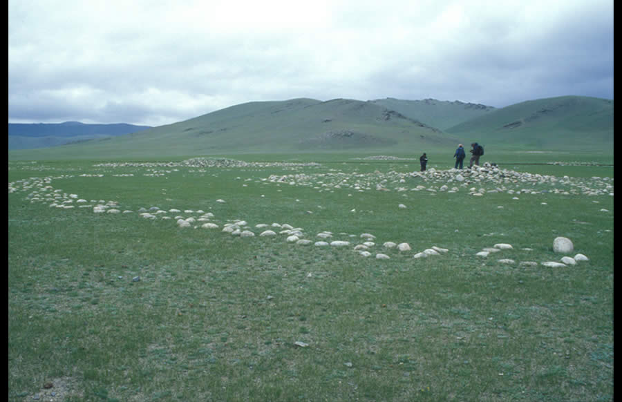 Small circles surrounding a khirigsuur. Tsagaan Asgat. View northwest.Small circles were apparently used for sacrificial burned offerings, perhaps over a period of several thousand years. They are found alone or on the east side of standing stones or in multiple numbers on the north, west, south, and occasionally east sides of khirigsuur. It is not possible to date them except be reference to organic materials found within or around them. The small circles typically surrounding khirigsuur may represent gradual additions over several generations or even centuries.