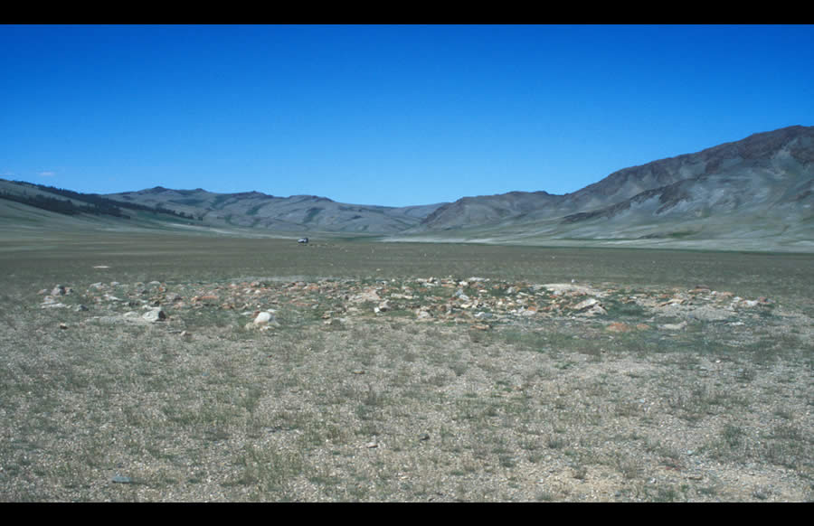 In a valley north of Mogoityn Gol, enclosures (background) and balbal face east to a ruined khirigsuur (foreground). Turkic period, Bronze Age.