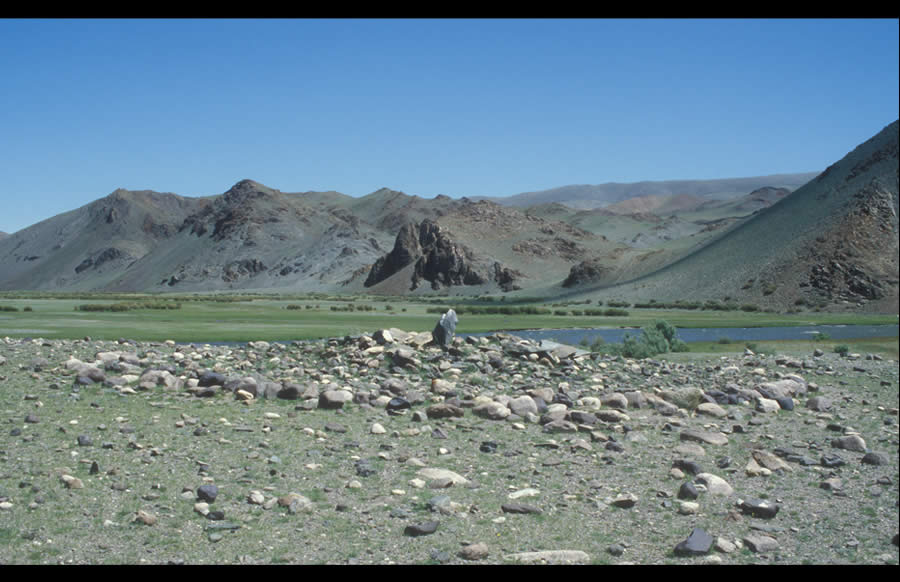 Round platform khirigsuur with central standing stone and multicolored boulders; left bank Sagsay Gol. Bronze Age.