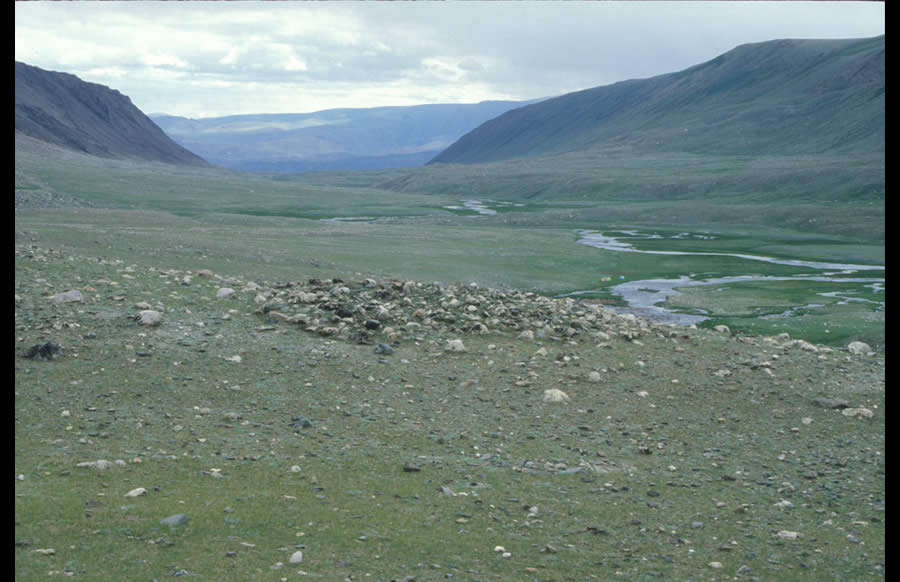 Old mound (11 m diameter) on a terrace above the left bank of Khöltsöötiin Gol. To the east its view shed includes the down river flow; to the west it includes Tsengel Khairkhan Nuuru. Bronze Age.