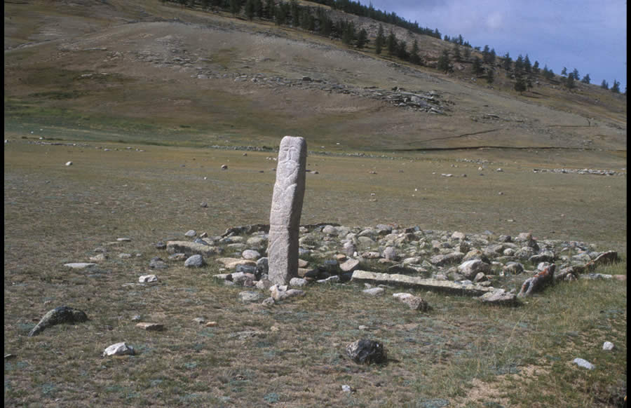 Tall Turkic image stone carved from a deer stone of the Late Bronze Age; a number of the enclosure's framing stones seem, also, to have originally been deer stones. Mogoityn Am, valley of Mogoityn Gol.