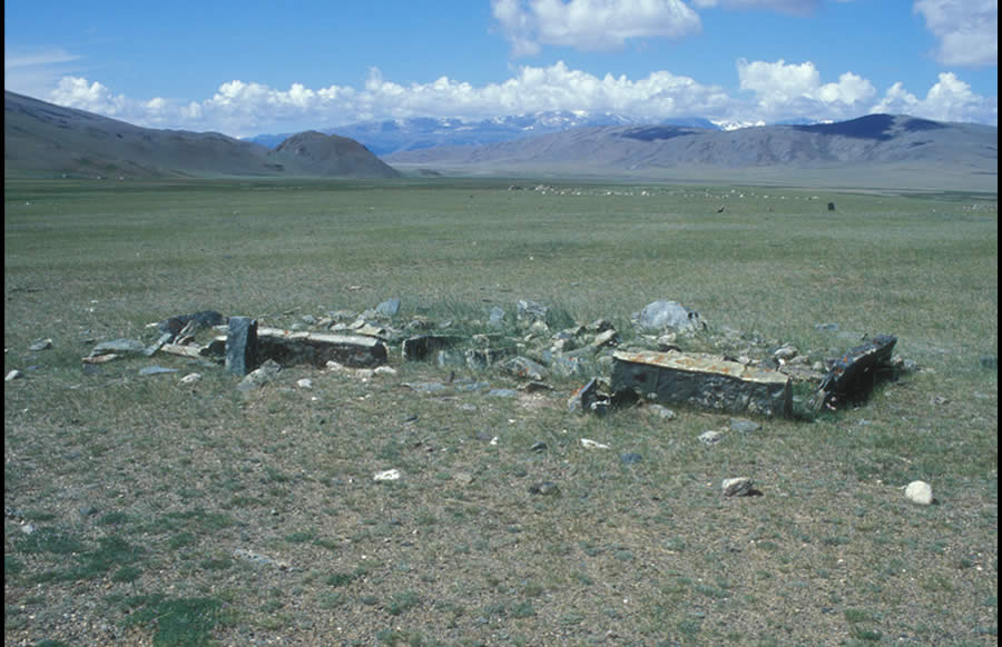 Two enclosures with broken frames and one false image stone. Turkic period. Khara Zharyk, Dayan Nuur Basin. View southwest.<p>False image stones are simple, un-carved, or barely carved vertical stones placed in the same way as true Turkic image stones on the east side of or within a Turkic enclosure. Their function was certainly similar to that of the true Turkic images; that is, they referred to specific deceased individuals.</p>
