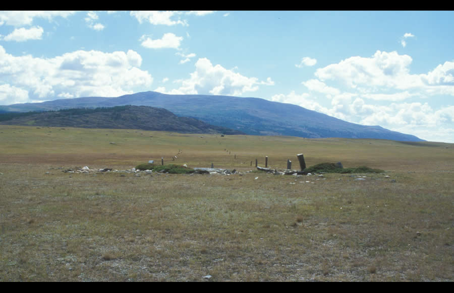 Three Turkic enclosures seen from the west. Enclosures have been disrupted over time and filled in with juniper. Three false image stones stand on the east sides of the enclosures, and two lines of tall balbal stretch to the east for a distance of 198 m. Khoton Nuur. Enclosures are squared or rectangular mounds, usually filled with white and black boulders and framed by black or granitic slabs. Enclosures are oriented with their sides to the four quarters. Excavations of enclosures in other regions have indicated that they were originally centered by a pit into which were probably poured ritual libations. The remains of larch poles in these pits and sometimes at one of the sides of the enclosure indicates the ancient mounting of young trees or poles for ritual purposes.