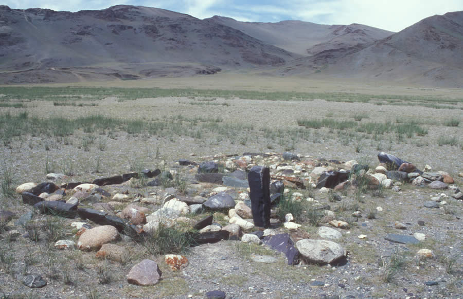 Two Turkic enclosures with frames of heavy, black slate, interior of mounded boulders. Both measure approximately 2 m to a side. The southern enclosure has a large standing false image stone with possible slight carving around the face. View here is from the southeast. Khargantyn Gol. Enclosures are squared or rectangular mounds, usually filled with white and black boulders and framed by black or granitic slabs. Enclosures are oriented with their sides to the four quarters. Excavations of enclosures in other regions have indicated that they were originally centered by a pit into which were probably poured ritual libations. The remains of larch poles in these pits and sometimes at one of the sides of the enclosure indicates the ancient mounting of young trees or poles for ritual purposes.