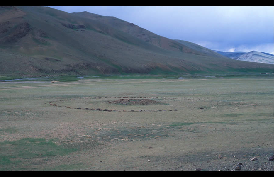 Round khirigsuur. D. 40 m (approximate). Bronze Age. Confluence of Khar Yamaa and Sailagiin Gol. View west to Khar Yamaa. Round khirigsuur range in size from approximately 10 m to over 40 m in diameter.  They are usually located on broad plains, along rivers, or at the confluence of rivers. They may appear alone or with other structures from the Bronze Age and later.