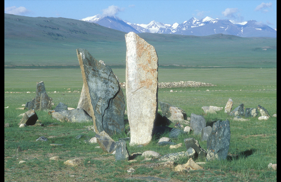 Deer stones within large group of standing and fallen stones, khirigsuur, and circular altars. Late Bronze Age. Tsagaan Asgat. View to south.Deer stones are large standing stones carved with a variety of distinctive elements. The classical Mongolian deer stone is marked by images of stylized, elongated deer on its wide sides. There may also be disks pecked into either of its wide sides and a line of beads (necklace) at its neck. Deer stones of the Sayan type may be marked with more realistic images of horses and ibex, and with belts, weapons, and shields. Those of the Altai type are simpler, with only necklaces, earrings, and slashes across the upper east side to indicate a face. Like massive standing stones, deer stones may be raised individually or set into north–south rows. On rare occasions, deer stones appear within a row of balbal associated with Early Nomadic burials. Their high narrow faces are almost always oriented to the east. The function of deer stones remains unclear but their anthropomorphic reference is certainly significant. Deer stones can be dated to the Late Bronze or Early Iron Ages.