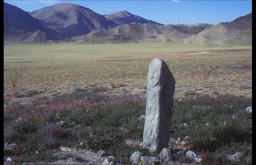Image stone with carved face, within broken frame in secluded valley. Late Bronze Age. Upper Sogoo Gol Valley. Within mountainous Bayan Ölgiy, there are only four or five documented standing stones with human faces from the pre-Turkic period, and of these three are also deer stones. In two cases the stones are oriented to the east; a third faces the north, a fourth has fallen, and the fifth faces south. These image stones date from the Late Bronze or Early Iron Ages. Their clear human appearance may shed light on the essential anthropomorphic reference of the massive standing stones.