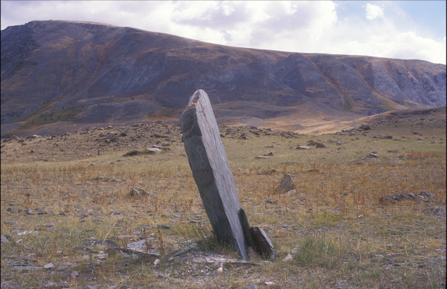 Standing stone in broken frame; tamga pecked into stone's north side. Stone ht. approximately 1.75 m. Bronze Age. Upper Tsagaan Gol. View southeast.Massive standing stones are typically located at the juncture of two valleys, or on high points commanding views to the east or south, or over rivers. The stones may be single or in groups of two or more arranged in rows from north to south and set within rectangular frames. <Small circles on the east side of their frames indicate that the direction east held a particular importance. The actual function of the stones is uncertain. Most were probably raised during the Bronze Age. Tamga can be found on some massive standing stones.
