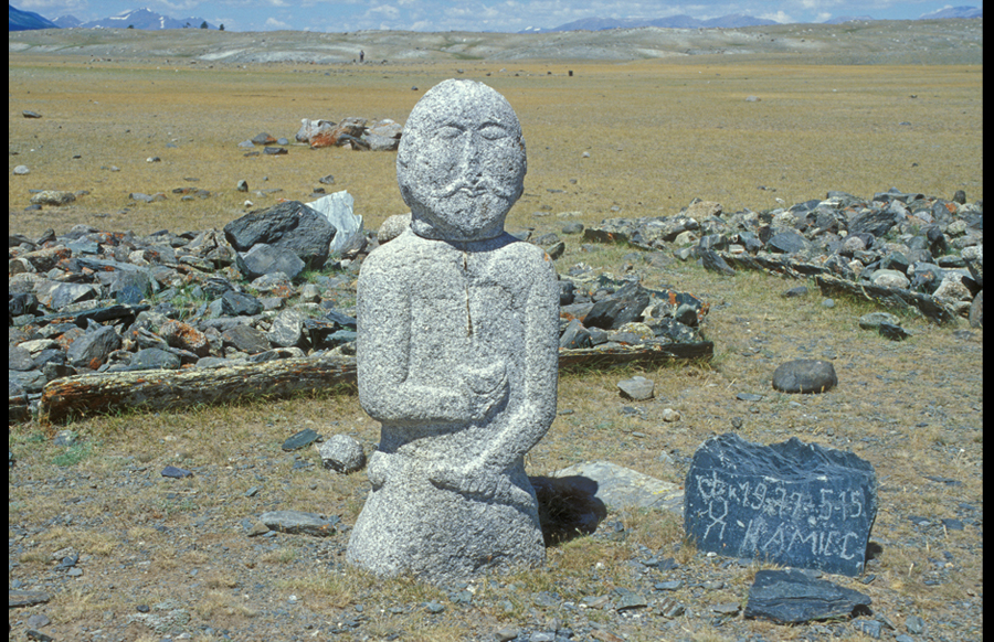 Image stone, one of four in front of four enclosures with two long lines of balbal. Ht. 1.12 m. Turkic period. South shore Khurgan Nuur. View northwest.Turkic image stones are of varying size and refinement, ranging from stones that are barely carved to images of clear human reference. Within the Mongolian Altai, the images are always male. In the more finished cases, the image is represented wearing a belted jacket; his right hand holds a cup in front of his chest, his left hand clasps his belt or a hanging weapon. Facial features may be shown as well as a mustache, small beard, and earrings. Images of the Turkic period stand on the east side of an enclosure or within it, facing east. Images from the late Turkic or Uighur period are never associated with enclosures. They wear long robes and clasp a vessel with both hands in front of their chests. Whichever their style, Turkic image stones appear to be memorial in function, but the individuals they memorialize are unknown. They are rarely associated with any obvious burials.